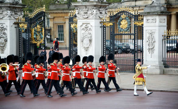 Soldiers parading past the ornate gates of Buckingham Palace in London/