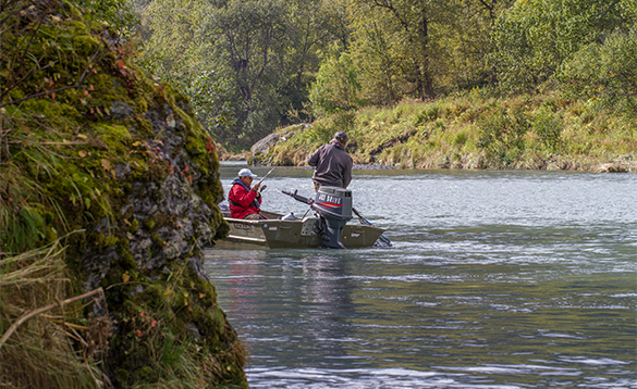 Two anglers fishing from a boat on a river in Alaska/