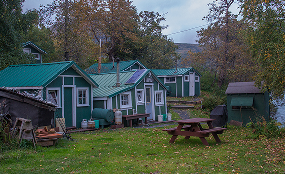 Green wooden cabins at a self-catering camp in Alaska/