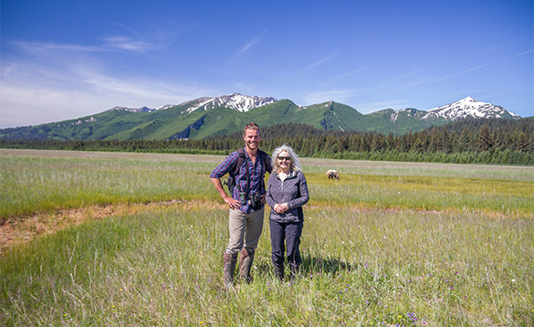 Lady standing with guide on grassland with mountains in the background and a grizzly bear walking behind them/