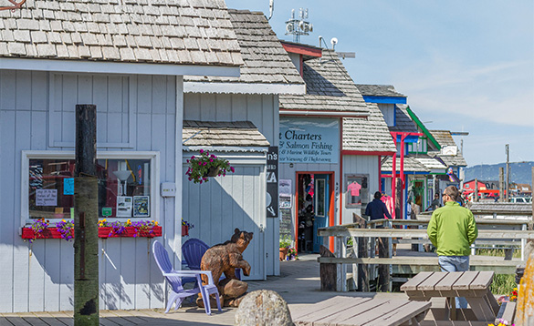 People walking along wooden sidewalks beside colourfully painted shops in Alaska/