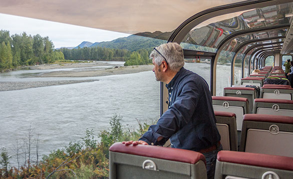 man standing on a train with arched clear windows and ceiling looking at a river flowing though forested hills/