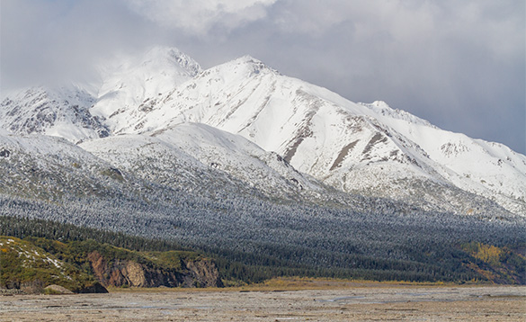 snow covered mountain leading to a sandy shoreline/