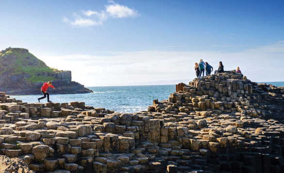 Group of children playing on the Giant's Causeway in Northern Ireland/
