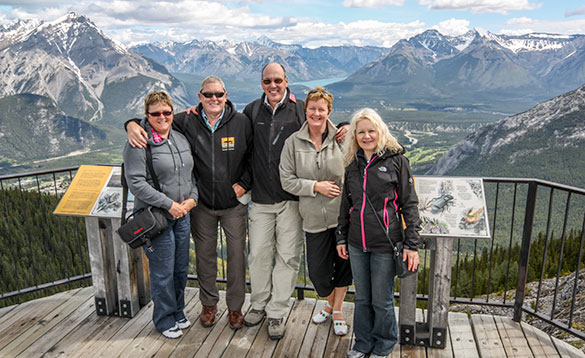 group of adults posing on a viewing platform looking out over snow capped mountains/