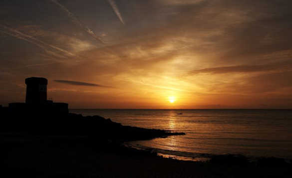 Sun rising over the sea beside the Archirondel Tower in Jersey/