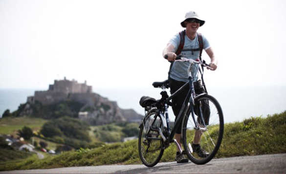 Cyclist walking up a hill pushing a bike with Mont Orgueil Castle in the background/