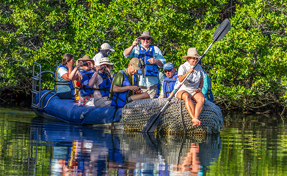 group of people on an inflatable boat travelling along a river/