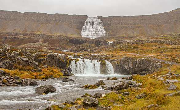 Waterfall cascading over craggy mountains in Iceland/