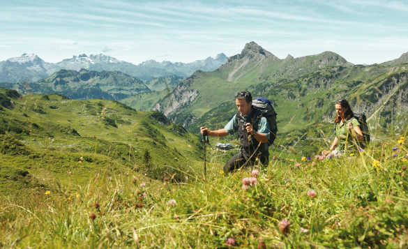 Hikers walking through the grassy hills of Steinernes Meer Vorarlberg in Austria/