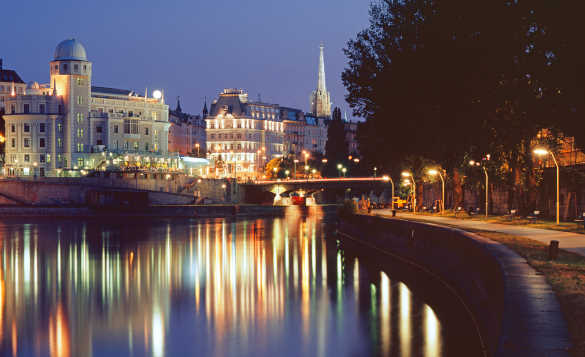 The Danube flowing past the brightly lit buildings of Vienna at night/