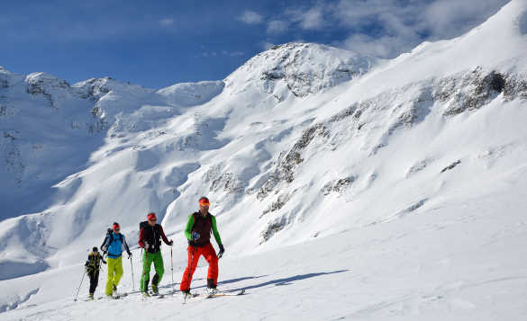 Cross country skiers skiing past snow covered mountains in Salzburgerland, Austria/