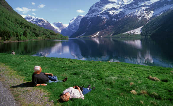 Couple relaxing on grass looking at Loen Lake and snow capped mountains in Norway/