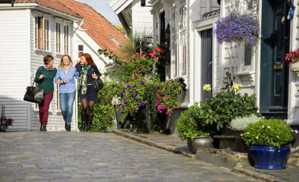 Group of woman walking along a cobbled street in Old Stavanger, Norway/
