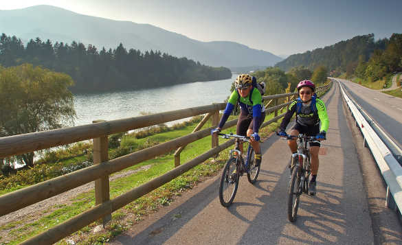 Two cyclists biking beside the River Drava in Slovenia/