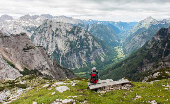 Man sitting on a seat looking across the craggy mountains and Trenta Valley in Slovenia/