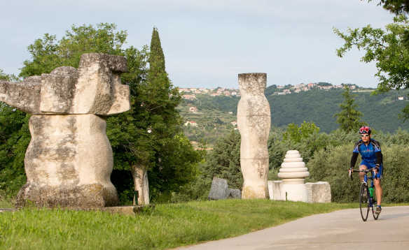 Cyclist biking past stone sculptures in Portoroz, Slovenia/