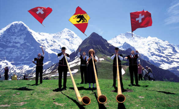 People blowing alpine horns and waving flags in front of snow capped Alps in Switzerland/