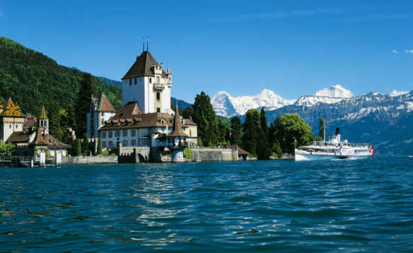 View across Lake Thun to a paddle steamer passing Oberhofen Castle in Stwzerland/