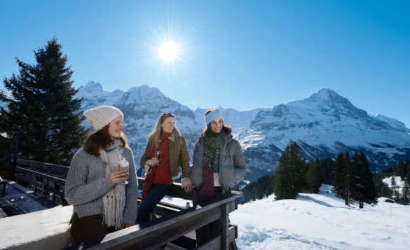 Group of people on a balcony drinking and enjoying view of the snow covered Bernese Alps and the Eiger/
