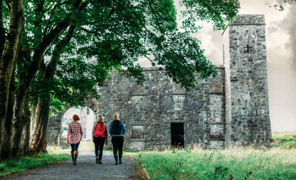 Group of people walking along a pathway to the ruins of Fore Abbey/