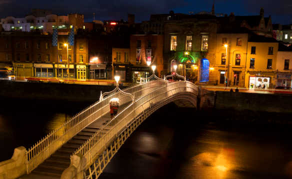 Night time view of the Ha'penny bridge in Dublin spanning the River Liffey/