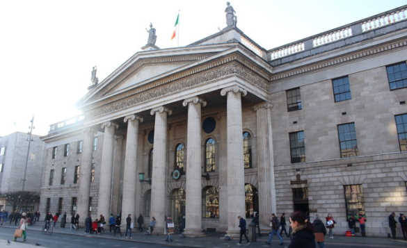 People walking past the stone built GPO building in Dublin/
