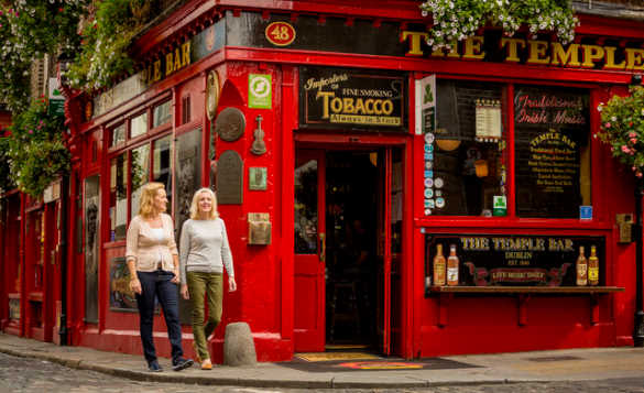 Two ladies walking past the red painted Temple Bar in Dublin/