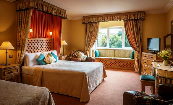 Luxurious bedroom at the Dingle Benners Hotel with double bed with canopy and window seat/