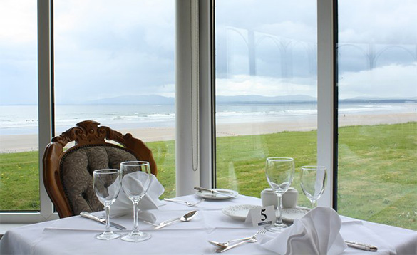 Table set for evening meal in the dining room at Sandhouse Hotel, Donegal with views across to waves breaking on a sandy beach/