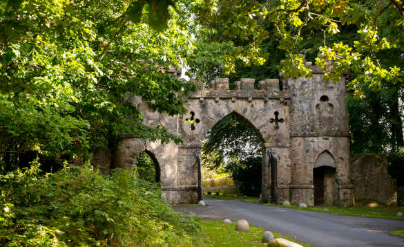 Stone castellated gateway with two round towers leading into Tollymore Forest Park in Northern Ireland/