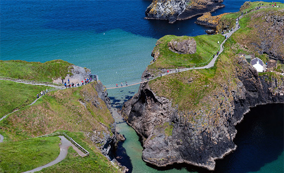 People crossing the Carrick-a-rede rope bridge leading to Rocky Island/