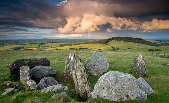 a stormy sky over fields with large rocky outcrops/