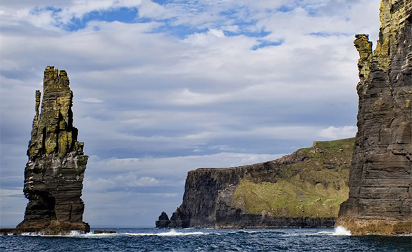 rocky shoreline with cliffs and a tall pointed outcrop raising from the sea/
