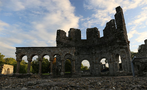 ruins of a stone abbey with arched windows/