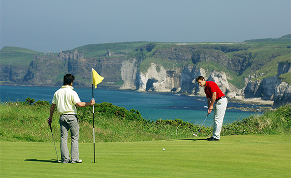 Two golfers putting on a green at Royal Portrush Golf Club/