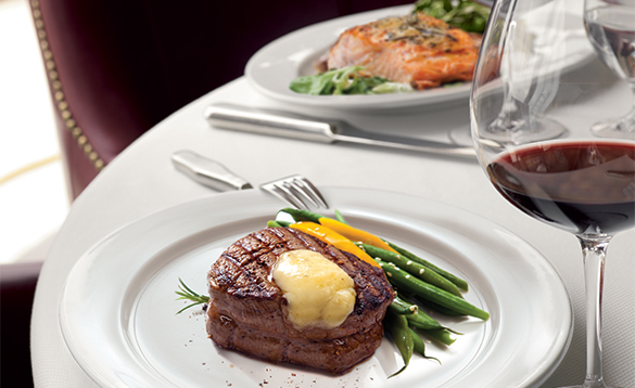 Dinner plate with steak and vegetables next to a glass of wine/