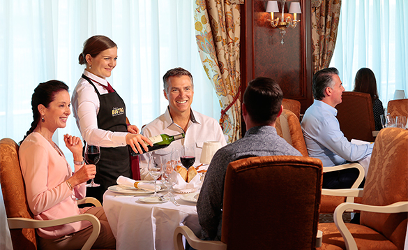 Waitress serving wine for passengers dining in Jacque's Bistro onboard an Oceania cruise ship/