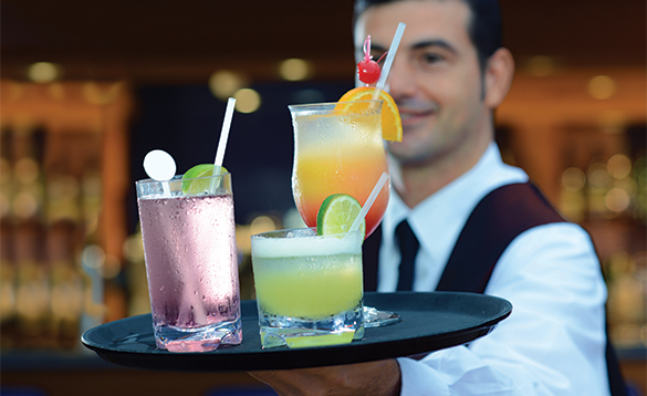 Waiter carrying three cocktails on a tray/