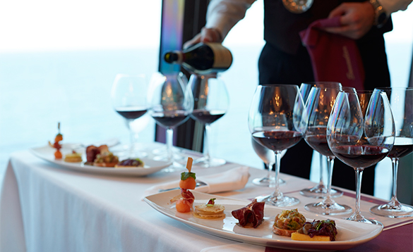 Waiter pouring wines for a wine tasting event onboard an Oceania cruise ship/