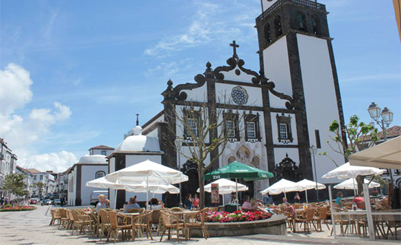 people sitting at cane tables and chairs with umbrellas in a town in Portugal beside a white painted church /
