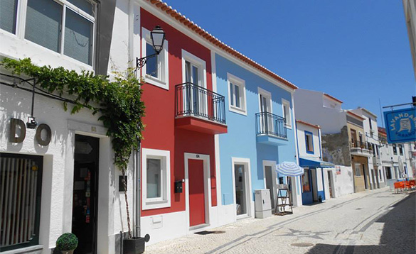 street in Potugal with row of brightly painted two storey houses/