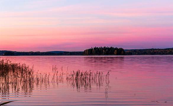 sun rising over islands turning sky pink and reflecting in a lake/