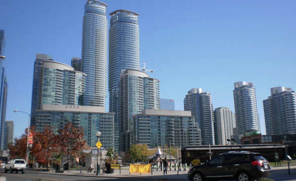 cars driving past skyscrappers in a city in Canada/