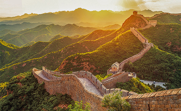 Great Wall of China meandering across hills and bushes/