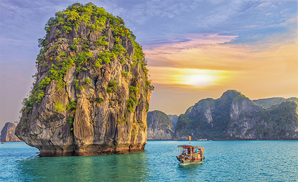 wooden boat travelling past a rocky limestone island with tropical jungle growing on it in Vietnam/