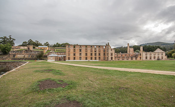view across lawns to an abandoned four storey brick building with no roof/