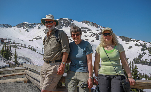 three people standing in front of snow covered mountains/