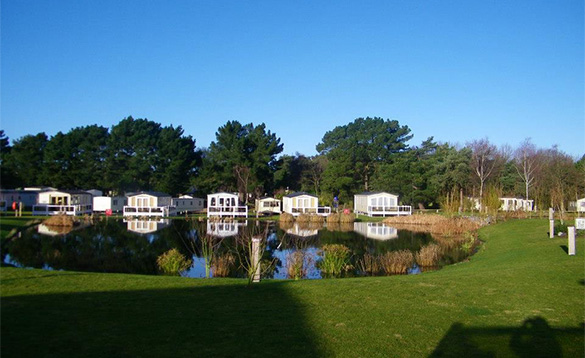 caravan site with a row of white caravans beside a lake and with trees in the background/