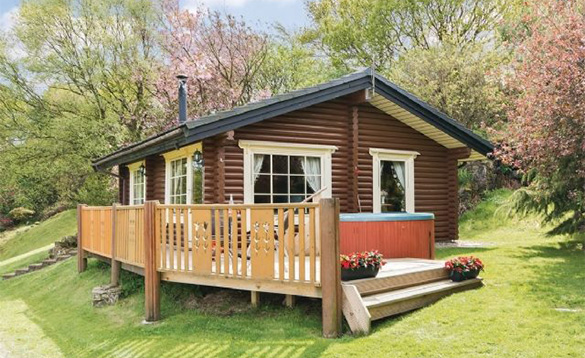 log cabin with wooden decked balcony to the front set amongst trees with pink blossom/